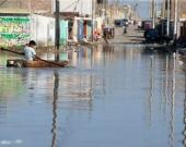 Un niño damnificado se desplaza sobre una pequeña balsa por una calle inundada de la ciudad de Huarmey en la región costera de Ancash (Perú). Foto: EFE.