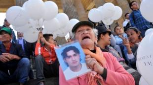 Una mujer enseña una foto de un familiar desaparecido. Foto: Guillermo Legaria / AFP