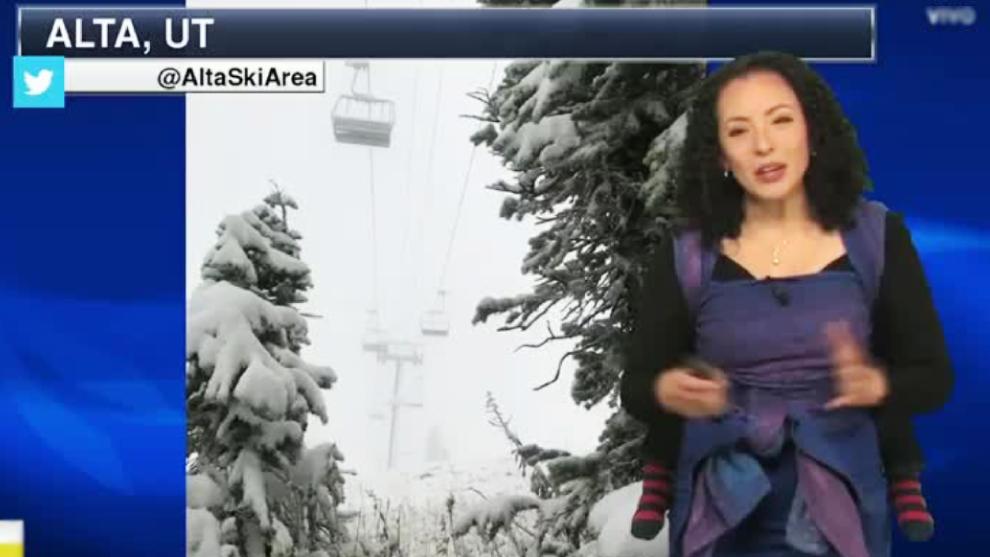 Mujer presenta el clima en televisión con su hijo en la espalda